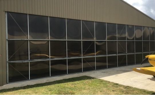 Tilt-over hangar doors